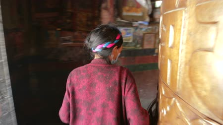 bodhnath : Woman touches spinning Big Tibetan Buddhist prayer wheel