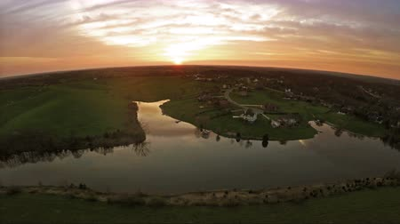 окрестности : Residential subdivision and a farm by a lake in Central Kentucky at sunset