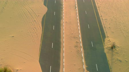 tarmac : Sand is taking over a desert road near Dubai in UAE. Aerial view