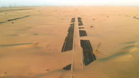 Sand is taking over a desert road near Dubai in UAE. Aerial view