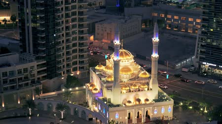 Mosque with modern buildings in the backdrop in Dubai Marina after sunset