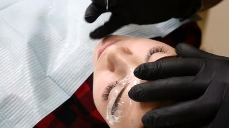 agulha : Beauty salon. Close up of Male beautician in black gloves making permanent makeup procedure on female eyebrows. Young woman gets facial beauty procedure. Facial rejuvenation. Using tattoo machine. Brow correction.