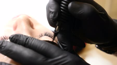 corrections : Beauty salon. Close up of Male beautician in black gloves making permanent makeup procedure on female eyebrows. Young woman gets facial beauty procedure. Facial rejuvenation. Using tattoo machine. Brow correction.