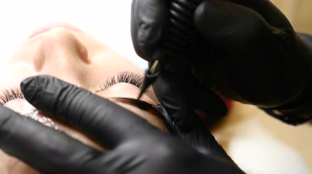 bőrápolás : Beauty salon. Close up of Male beautician in black gloves making permanent makeup procedure on female eyebrows. Young woman gets facial beauty procedure. Facial rejuvenation. Using tattoo machine. Brow correction.