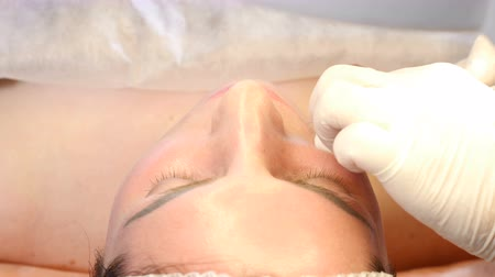 botulinum : Beauty clinic concept. Close-up of beautician hands making   injection to female lips. Young woman gets facial injection procedur.. Facial rejuvenation. 4k