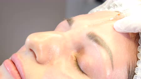 contornos : Beauty clinic. Beautician hands in gloves making face aging injection to a female skin. A woman gets beauty facial cosmetology procedure. injection to female forehead. collagen injections. 4k Vídeos