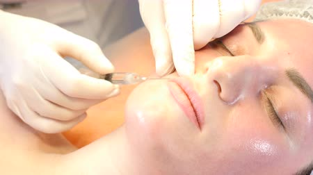 botulinum : Beauty clinic concept. Close-up of beautician hands making injection to female lips. Young woman gets facial injection procedure. Facial rejuvenation. 4k