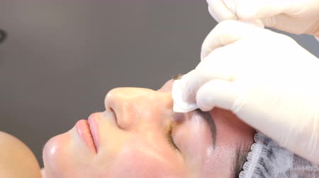 contornos : Beauty clinic. Beautician hands in gloves making face aging injection in a female skin. A woman gets beauty facial cosmetology procedure.  collagen injections. Shot in 4k