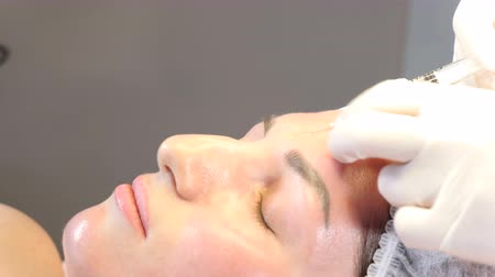 botulinum : Beauty clinic. Beautician hands in gloves making face aging injection in a female skin. A woman gets beauty facial cosmetology procedure. collagen injections. Shot in 4k