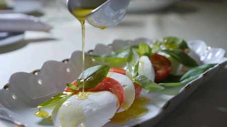 olive oil pour : Healthy food and vegetarian concept. Close up of Pouring olive oil over caprese salad. Italian caprese salad with Mozzarella cheese. Slow motion Stock Footage