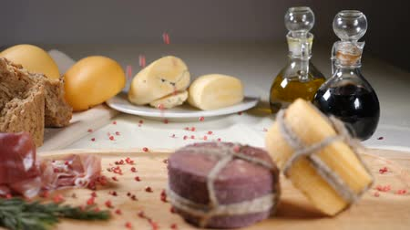 sedir : Restaurant concept. Table setting. Two pieces of cheeese decorated with rope are on wooden background with home made bread, nuts and olive bottles. Nuts and pepper fall down. Slow motion.