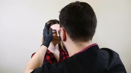 düzeltme : Male beautician in black gloves making permanent makeup procedure on female eyebrows. Beautician cosmetologist in healthcare clinic cabinet of beauty salon. using rule of golden ratio in cosmetology Stok Video
