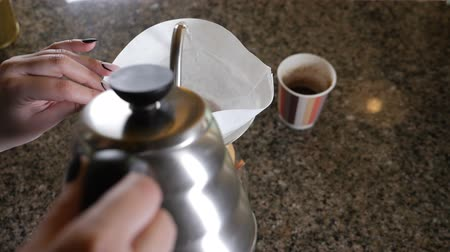 brew coffee : Modern and alternative ways of coffee making.Barista brews coffee using Coffee maker Chemeks. Close up of hands pouring hot water out of pot into paper filter with Coffee. Slow motion