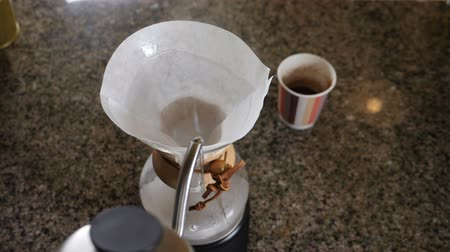 csöpögő : Modern and alternative ways of coffee making.Barista brews coffee using Coffee maker Chemeks. Close up of hands pouring hot water out of pot into paper filter with Coffee. Slow motion