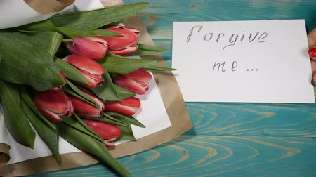 perdão : Top view of a forgive me message and Tulips flowers bouquet on a wooden table. Couple relationship concept. Shot in 4 k Vídeos