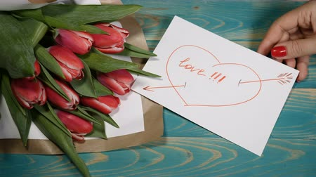 perdão : Top view of a I Need You message note and Tulips flowers bouquet on a wooden table. Love relationship concept. Saint Valentines Day. Shot in 4 k
