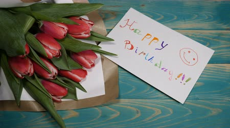 я тебя люблю : Top view of a Happy Birthday message note and Tulips flowers bouquet on a wooden table. Love relationship concept. Birthday consept. Shot in 4 k Стоковые видеозаписи