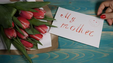 я тебя люблю : Top view of a My Mother message note and Tulips flowers bouquet on a wooden table. Love relationship concept. Mother day. Shot in 4 k Стоковые видеозаписи