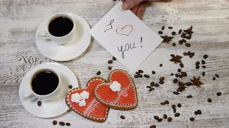 kávové zrno : Love relations. St. Valentine concept. Top view of Two cups of coffee and two ginger biscuit heart shaped are on wooden background with coffee beans around. Female hand puts I love You message note, 4 k