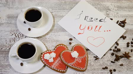 szív alakú : Top view of a I need You message note and two cups of coffee with heartshaped ginger biscuit on a wooden table. Love relationship concept. St Valentine s Day. Shot in 4 k