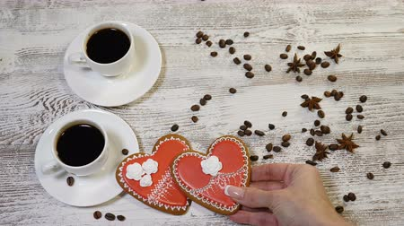 kávové zrno : Saint Valentine`s Day concept. Coffee in white cups, home made heart shaped ginger biscuit on wooden background. hand puts a one cookie on another , 4 k Dostupné videozáznamy