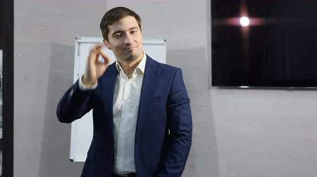 schválení : Portrait of handsome young businessman shows emotional gestures, thumb up, its ok and fuck finger. Business, office concept. Shot in 4 k Dostupné videozáznamy