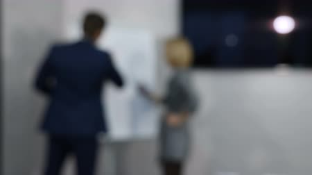 flip chart : Blurred, defocused, blur video. Successful business team busy working on a hand drawn graph on a flip chart. Planning, Discussing. Shot in 4k Stock Footage