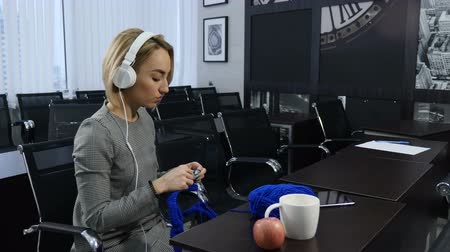 рукоделие : People, needlework, handycraft concept. Young pretty woman in headphones knitting with knitting needle and blue yarn. Smile. Lifestyle. Time spending, Leisure. Shot in 4 k