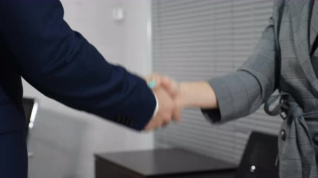 договориться : Office life concept. Close up of two unrecognizable male and female business partners shaking hands. Shot in 4 k