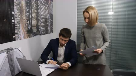босс : Office. Female secretary puts boss papers to be signed. Shot in 4 k