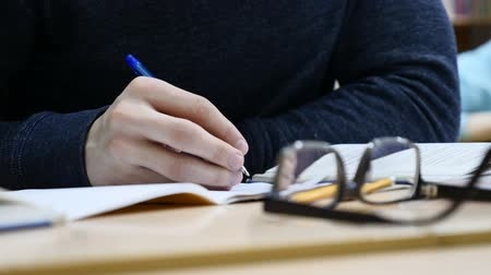 task : Close up of male journalist`s hands hold pen making notes at press conference. Looking glasses on table. Stock Footage