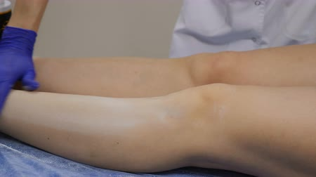 woman waxing : Beautician spteads hygienic powder on legs before hair removing procedure. Shot in 4 k. Close up