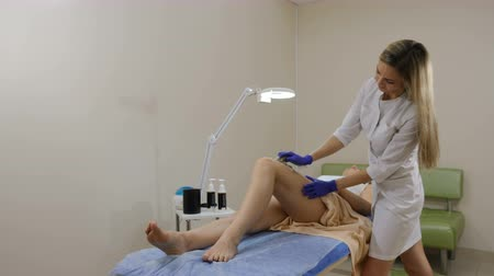 woman waxing : Beautician in gloves makes hair removal on a young woman s leg. Shot in 4 K Stock Footage