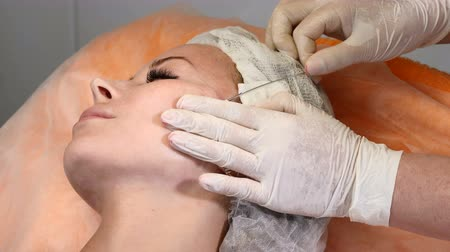 cosmetic surgery : Healtcare clinic. Young female client gets thread face lifting procedure. Beautician in gloves making face anti-aging to a female face Stock Footage