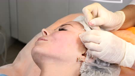 zmarszczki : Healtcare clinic. Young female client gets thread face lifting procedure. Beautician in gloves making face anti-aging to a female face Wideo