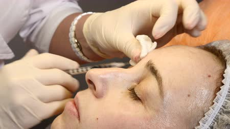 botulinum : Beauty clinic. Beautician hands in gloves making face anti-aging injection in a female skin around eyes. A woman gets beauty facial cosmetology procedure. collagen injections