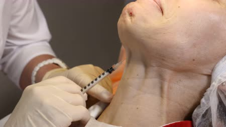 operacja plastyczna : Beauty clinic. Beautician hands in gloves making face anti-aging injection in a female neck. A woman gets beauty facial cosmetology procedure. Collagen injections Wideo