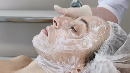 masażysta : Cosmetician in gloves applying cosmetic cleaning mask before facial beauty procedure. Wideo