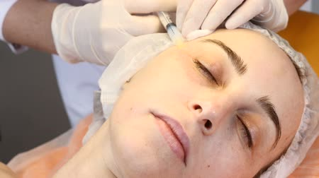 botulinum : Cosmetician in gloves making face lifting injection to area around eyes. female client gets facial beauty procedure in healthcare clinic. liquid thread injection.  collagen