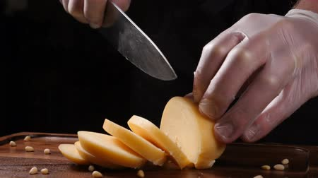 cheese slices : Chef in gloves slices cheese with a knife. Restaurant. Table serving