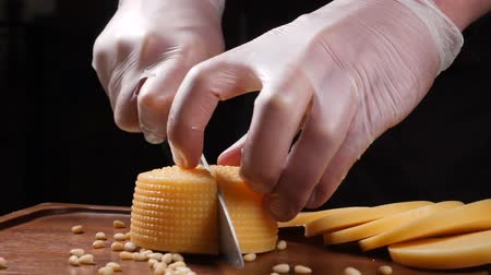 sedir : Chef in gloves slices cheese with a knife. Restaurant. Table serving. Food art