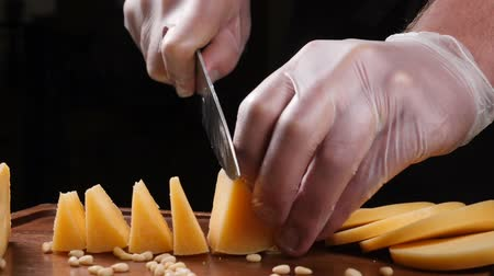orzechy włoskie : Chef in gloves slices cheese with a knife. Restaurant. Table serving. Food art