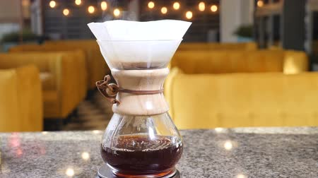 kaynatmak : Modern hand brewed coffee. Barista brews coffee using Coffee maker . Close up drops of coffee falling from paper filter into bowl. Slow motion Stok Video