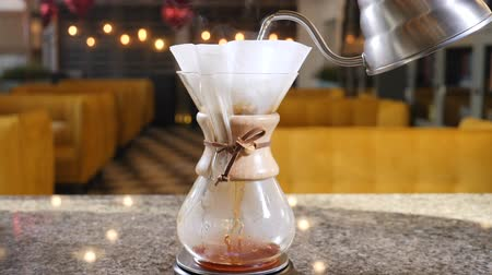 brew coffee : Modern and alternative ways of coffee making.Barista brews coffee using Coffee maker. Close up of hands pouring hot water into paper filter with Coffee. Slow motion