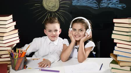 scholar : Back to School concept. Boy and girl sit at a desk with heaps of books and a blackboard with kids drawings behind them. Girl in headphones listening to music smiling