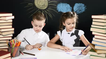 scholar : School concept. Cute children enjoy ssuccess sitting at a desk with heaps of books and a blackboard with drawings behind them. High five. Goal reach. 4k