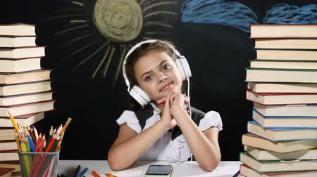 scholar : Modern school concept. Attractive girl sits at a desk with heaps of books. and a blackboard behind her. Schoolgirl in headphones smiles.
