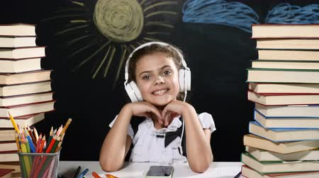 ders kitabı : Modern school concept. Attractive girl sits at a desk with heaps of books. and a blackboard behind her. positive schoolgirl in headphones smiles. thumbs up. Stok Video