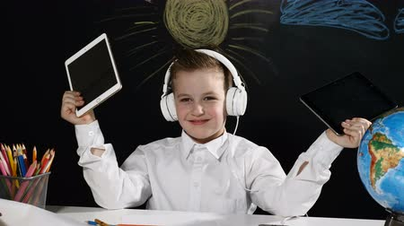 scholar : School concept. Cute boy sits at a desk with globe on it. and a blackboard behind him. positive schoolboy in headphones smiles with tablets in his hands
