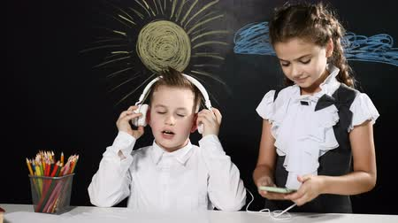 scholar : School concept. Cute boy and attractive girl sit at a desk and blackboard behind them. Schoolgirl puts headphones on boy and turns on music Stock Footage